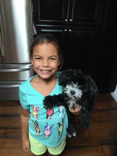 An image of Mareena standing in her kitchen with her small black and white dog smiling for the camera
