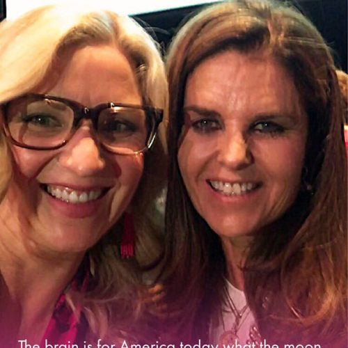 """A close-up photo of a blond woman wearing glasses standing next to a brown-haired woman wearing makeup. The bottom of the image fades to pink and includes a quote: """"The brain is for America today what the moon was for America in the 1960s: the next frontier."""" The quote is attributed to Maria Shriver. At the top of the photo is a purple brain logo and the words 'Mickie's Miracles Blog'."""